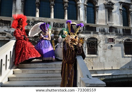 VENICE - MARCH 7: Group of  an unidentified masked persons in costume on the bridge via Venice canal during the Carnival on March 7, 2011. The 2011 carnival was held from February 26th to March 8th. - stock photo