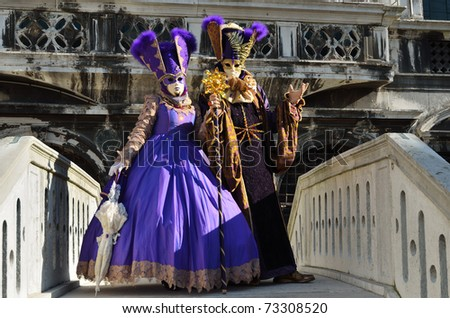 VENICE - MARCH 7: Two unidentified masked person in costume on the bridge via Venice canal during the Carnival on March 7, 2011. The 2011 carnival was held from February 26th to March 8th. - stock photo