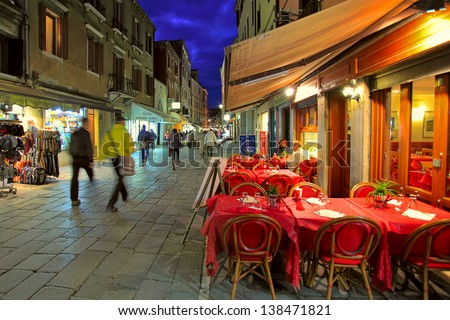 VENICE - NOV 13: Outdoor restaurant with red tables and chairs - one of the many bars and restaurants popular with tourists in the evening hours on streets of Venice, Italy on November 13, 2012. - stock photo