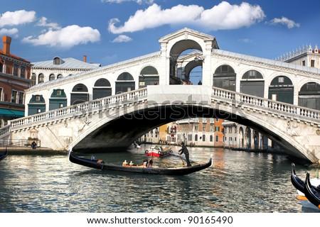 Venice, Rialto bridge with gondola in Italy - stock photo