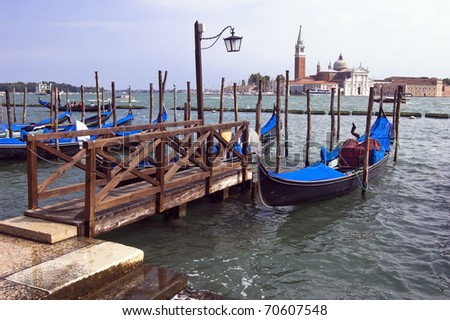 Venice's famous gondolas lined up in the lagoon with the island of San Giorgio Maggiore behind - stock photo