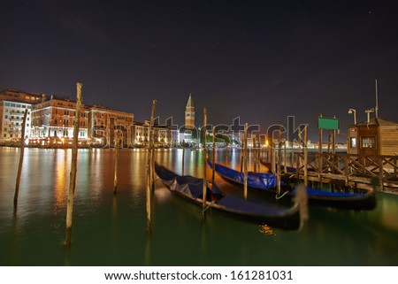 Venice, San Giorgio Maggiore church behind city Long exposure By Night. Blurred motion Gondolas due to Grand Canal sea movement. - stock photo