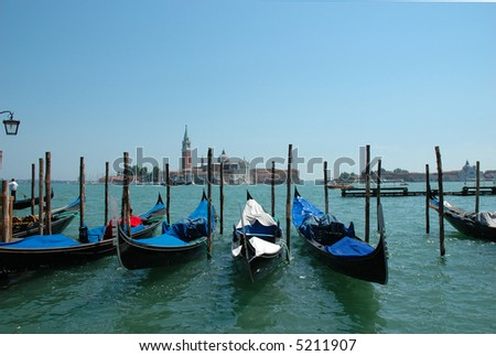 Venice- St. Giorgio in the background, with covered gondolas in the foreground - stock photo