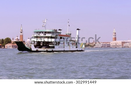 Venice, VE - Italy. 14th July, 2015: Ferry of ACTV company of Venice  to transport cars and vehicle from Venice Island to Venice Lido and the church of Saint George and Saint Mark Bell Tower