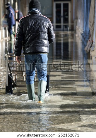 Venice Worker with the transport cart and the boots at high tide