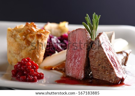 Venison meat steak with red cabbage, cranberries, herbs and Potato  - stock photo