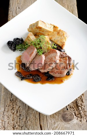 Venison steak cuts on a chestnut puree with dried plums - stock photo