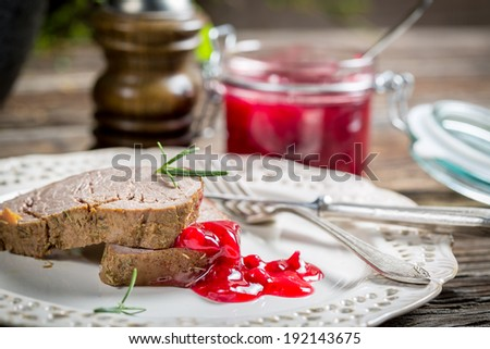 Venison with cranberry sauce on white plate - stock photo