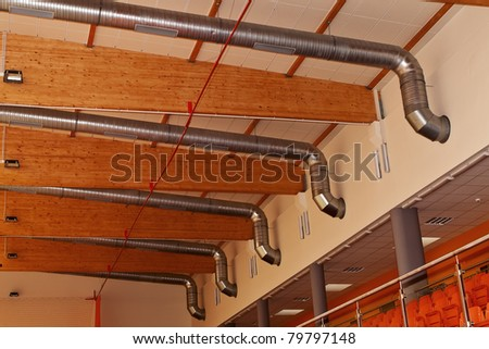 Ventilation and air-conditioning metal ducts under roof wooden construction. - stock photo