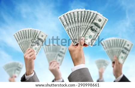 Venture capital or crowd funding finance and investment concept businessmen holding up dollar currency aloft - stock photo