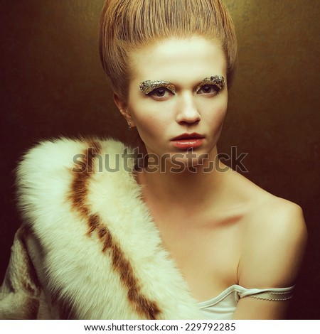 Venus in furs concept. Portrait of fashionable red-haired model with perfect arty make-up, vintage hairdo wearing luxury fur coat and posing over golden background. Retro style. Close up. Studio shot - stock photo