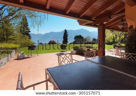 veranda of a villa with garden in a sunny spring day - stock photo