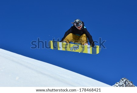 VERBIER, SWITZERLAND - FEBRUARY 21: Freestyle snoboarder performs a front grab: February 21, 2014 in Verbier, Switzerland - stock photo