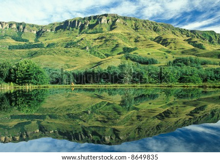 Verdant green slopes of the Drakensberg mountains reflected in the still waters of a lake. KwaZulu Natal, South Africa - stock photo