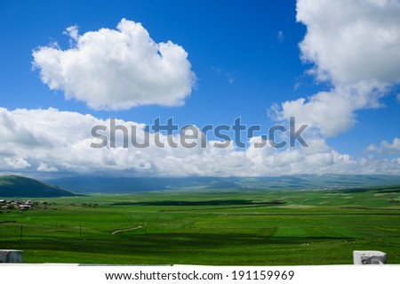 Verdant landscape along roadside with dramatic clouds - stock photo