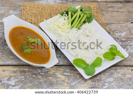 Vermicelli solution (Noodles) and fish curry coconut milk with vegetable on brown cloth background - stock photo