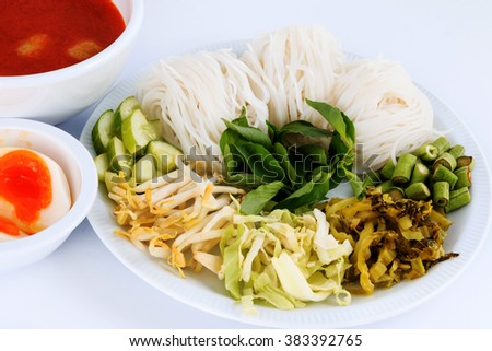 Vermicelli solution (Noodles) and fish curry coconut milk with vegetable on white  background.(Kanom Jeen Nam Ya) - stock photo
