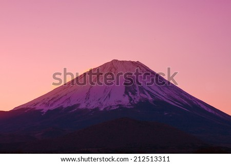 Vermilion sky and the summit of Mount Fuji, a world heritage in Japan - stock photo
