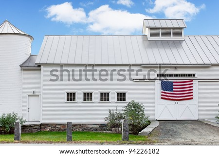 Vermont white dairy barn. Vintage 19th century barn with American flag hanging across the doors - stock photo