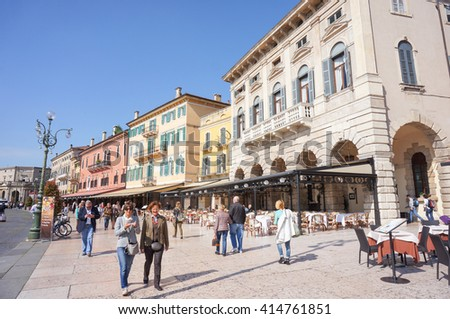 VERONA, ITALY - APRIL 20, 2016: Unidentified people walking along buildings with restaurants on a square in the city center on a sunny day - stock photo
