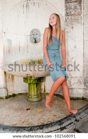 Verona, Italy - beautiful girl and historic fountain - stock photo