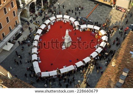Verona, Italy - February 14, 2013: People in the Dante Square , where a large red heart has been placed. For the Valentine's day Verona is transformed into the city of love. - stock photo