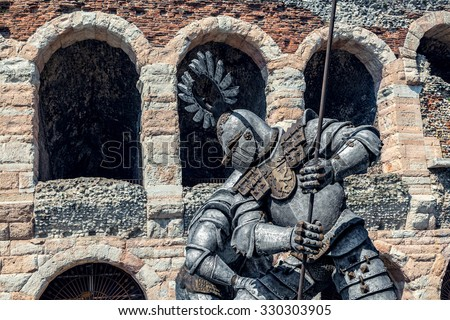 Verona, Italy - JUNE 07, 2013: In the foreground a sculpture of Gladiator. In the background ancient arena. - stock photo