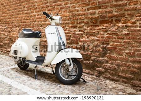VERONA, ITALY - MAY 16, 2014: Old Vespa parked on old street in Verona, Italy.  - stock photo