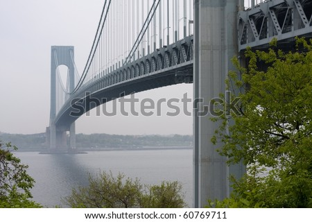 Verrazano Bridge in fog with green trees in foreground - stock photo