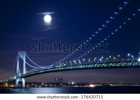 Verrazano Narrows Bridge with full moon in New York City at evening. It connects Brooklyn with Staten Island. - stock photo