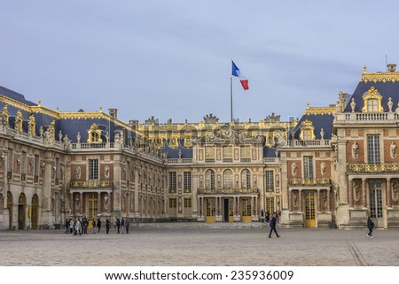 VERSAILLES, FRANCE - NOVEMBER 13, 2014: Tourists regard building of Palace at Versailles. Palace of Versailles was a royal chateau. It was added to the UNESCO list of World Heritage Sites.  - stock photo