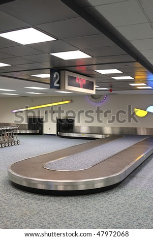 "Vertical Airport Baggage Claim Carousel.  Some carts on the left, top reads ""Welcome to"". Carousel is empty, before the bags are unloaded"