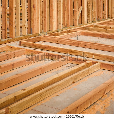 Vertical and horizontal boards on a concrete slab at a construction site. - stock photo