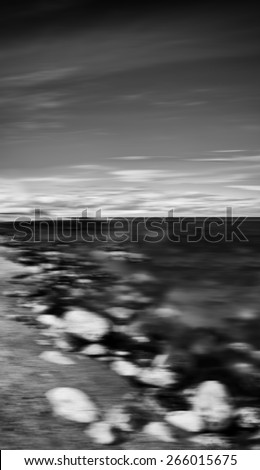 Vertical black and white dramatic stony beach motion blur abstraction background backdrop
