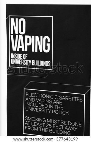 Vertical Black & White NO VAPING Sign Posted On Wall Of An American University College Dormitory Residence Hall Building
