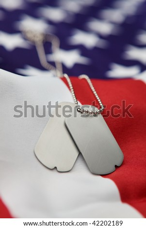 Vertical blank dog tags on American flag with focus on tags - Shallow dof - stock photo