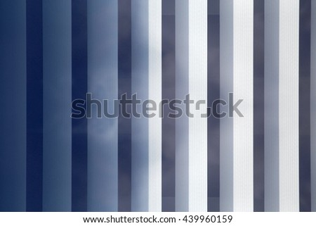 Vertical blinds / jalousie with reflection of sky. Modern interior / architecture photograph with regular stripy structure. - stock photo