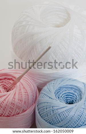 vertical blue, white and rose balls and hook for knitting