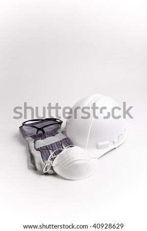 vertical centered hard hat medical face mask safety glasses and leather gloves - stock photo