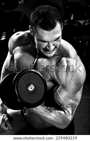 vertical close up portrait handsome guy bodybuilder ,  execute exercise with  dumbbells, in dark gym, balck and white photo - stock photo