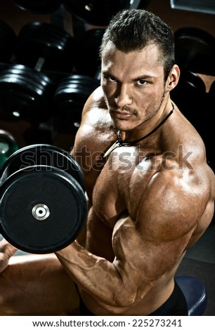 vertical close up portrait handsome guy bodybuilder ,  execute exercise with  dumbbells, in dark gym - stock photo
