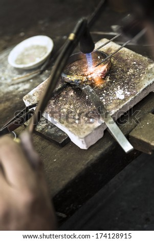 Vertical close up shot of Jeweler crafting golden bracelet with flame torch. - stock photo