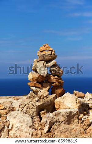 Vertical color image of a series of rocks stacked one over the other with a nice blue sky background. - stock photo