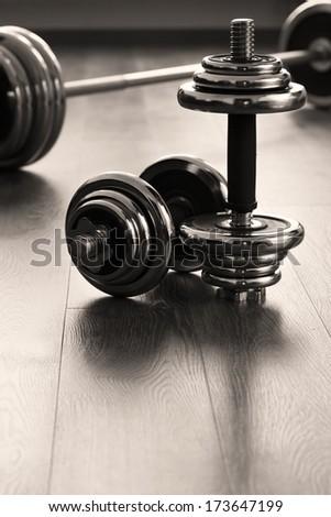 vertical dumbbells for fitness on wooden floor - stock photo