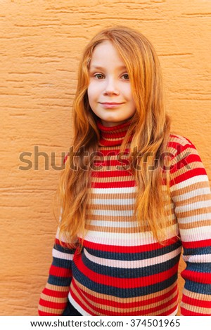 Vertical fashion close up portrait of adorable redheaded girl against orange wall, wearing stripes roll neck pullover - stock photo