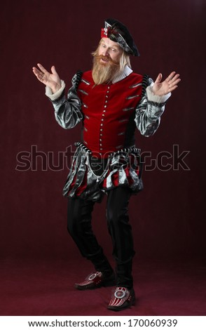 vertical full length portrait of an adult male with a beard and mustache in medieval costume and headdress studio on a burgundy background - stock photo