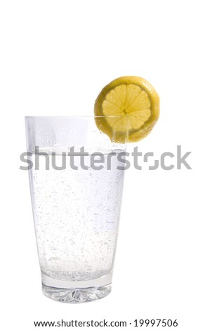Vertical high key image of a glass of sparkling mineral water with a lemon wedge.