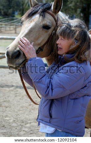 Vertical image of a Baby Boomer era woman showing affection to her horse. - stock photo