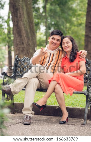 Vertical image of a bonding senior couple where a husband pointing at something  - stock photo