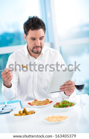 Vertical image of a businessman networking while having lunch inside - stock photo